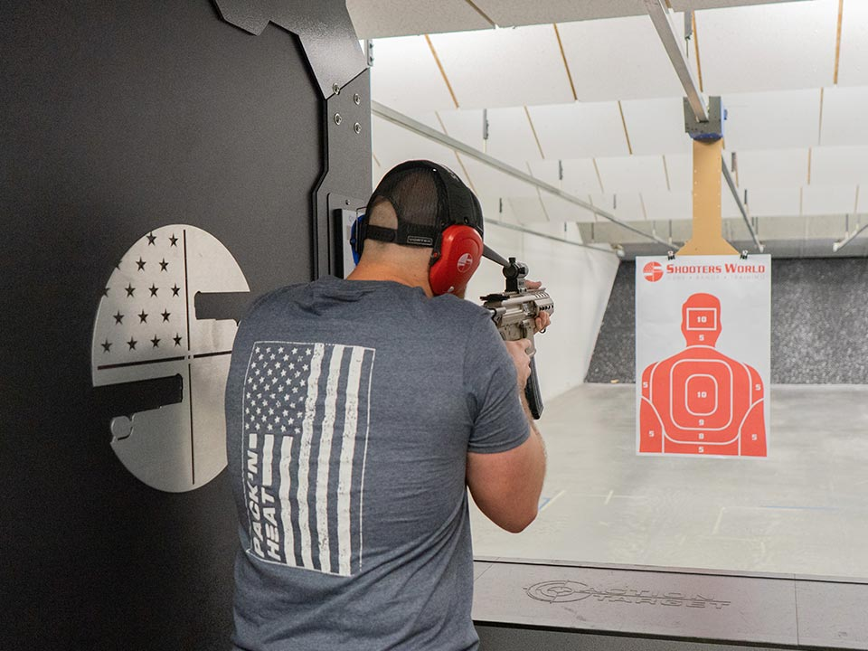 Guy in gray t-shirt shooting semi-automatic in range