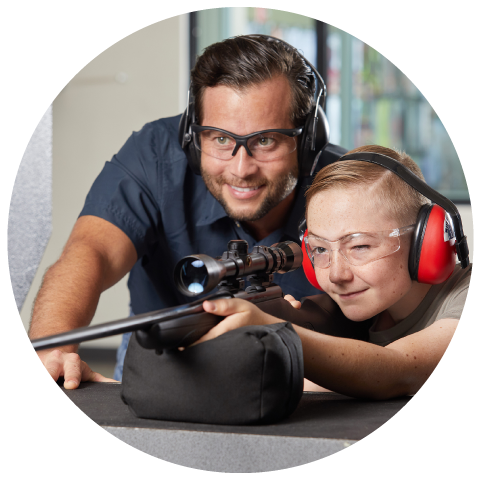 Firearms instructor helping kid file a rifle