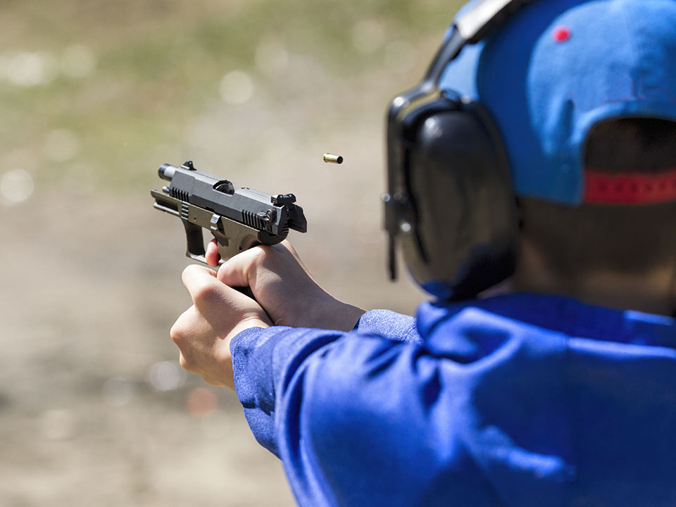Young boy in blue shirt and had shooting a handgun