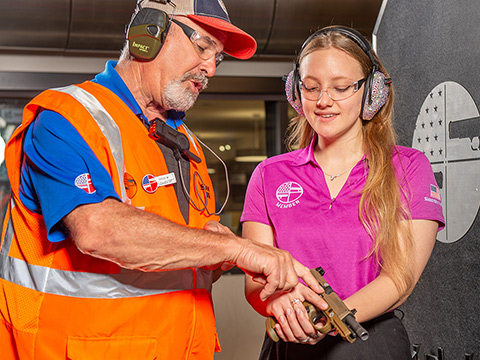 Young girl learning gun safety by male instructor