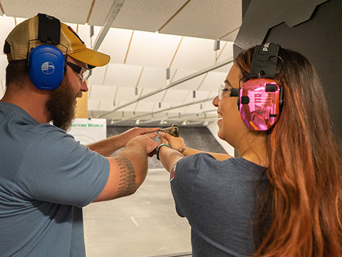 Woman in pink chrome earmuffs being trained on handgun